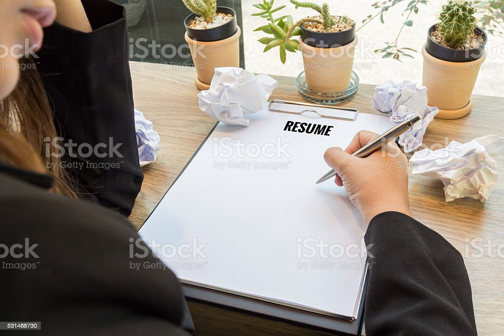 Woman hand writting resume in notebook with pen and paper stock photo