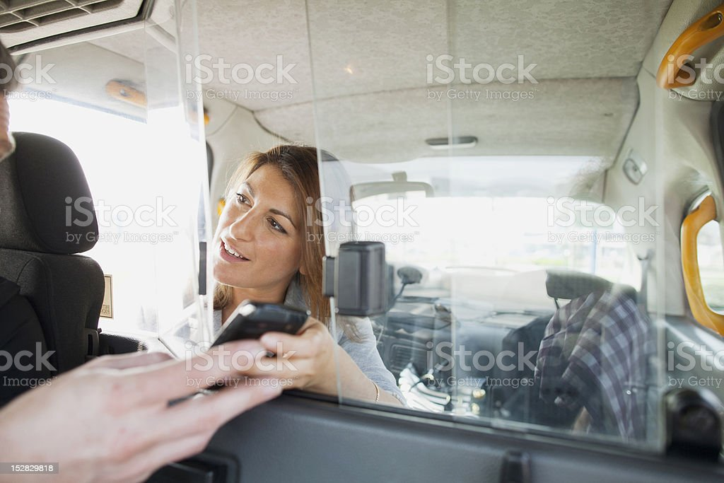 Woman handing cell phone to taxi driver stock photo