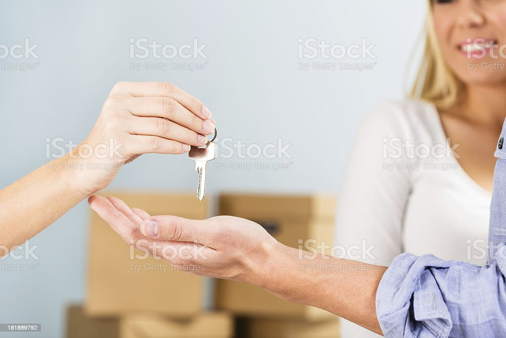 Woman handing over the house key royalty-free stock photo