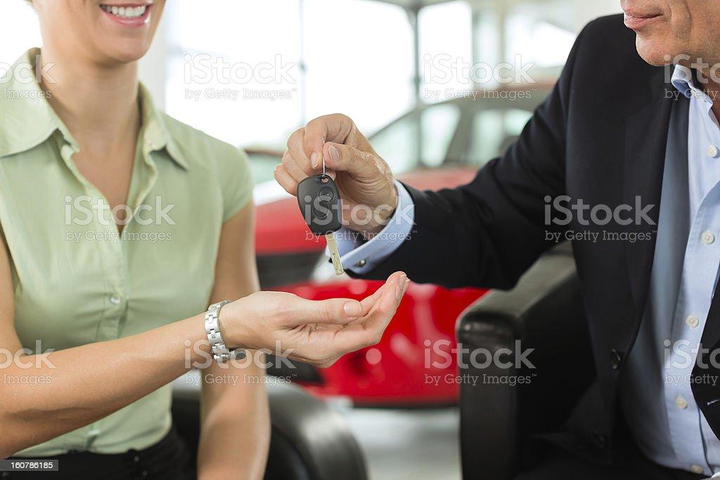 Woman hands car keys to man at auto dealer royalty-free stock photo