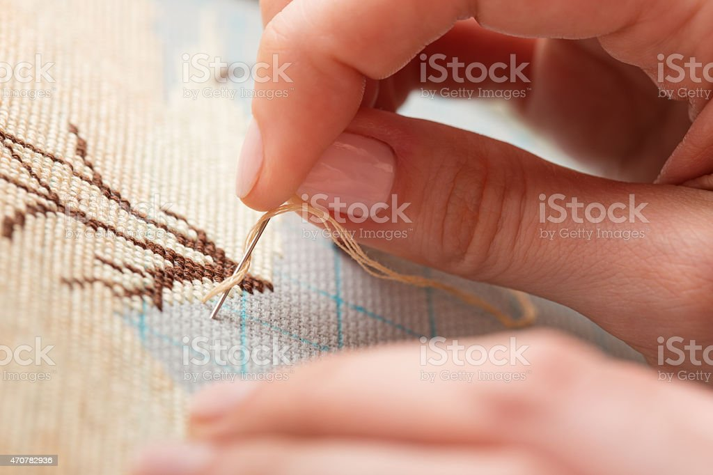 Woman hands doing cross-stitch. A close up of embroidery. stock photo