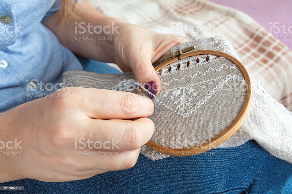 Woman hands doing openwork embroidery on homespun linen. stock photo