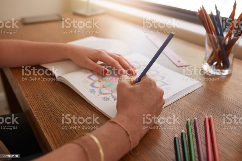 Woman hands drawing in adult colouring book stock photo