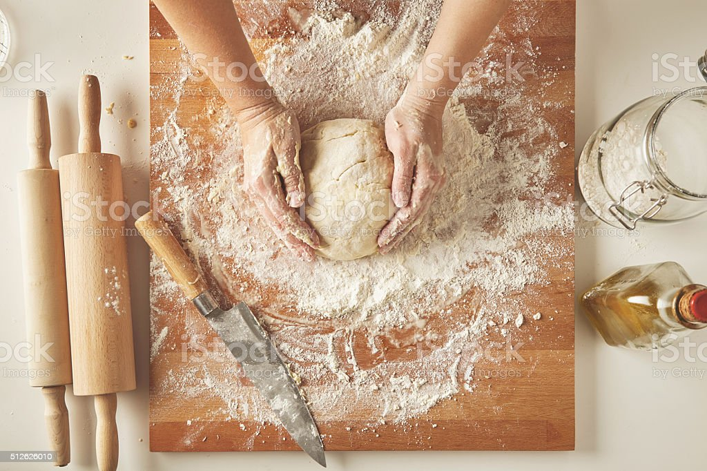 Woman hands hold prepared dough top view stock photo
