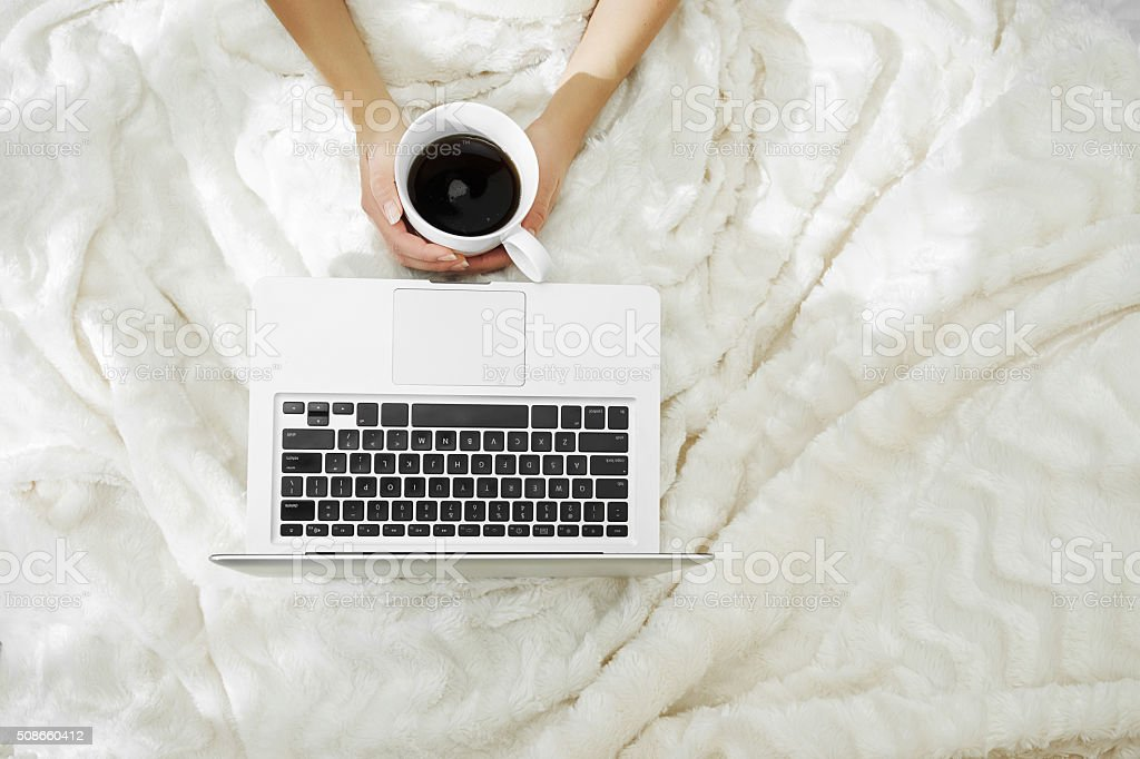 Woman hands holding a cup of hot coffee in bed stock photo