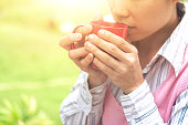 woman hands holding a red cup of coffee
