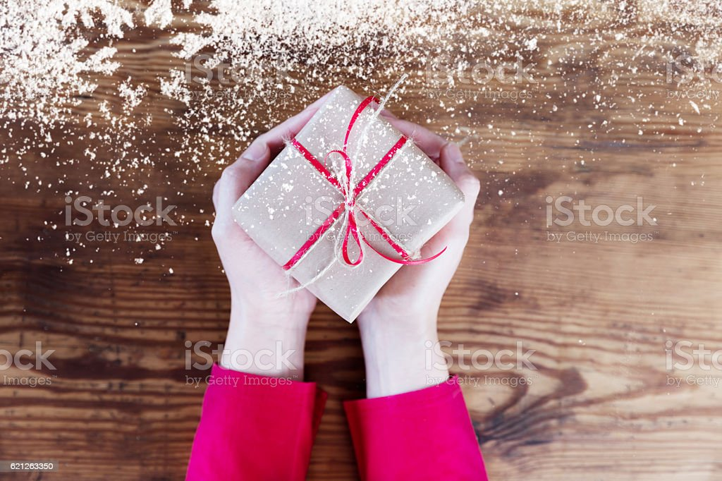 Woman hands holding christmas present with snowflake on wood stock photo