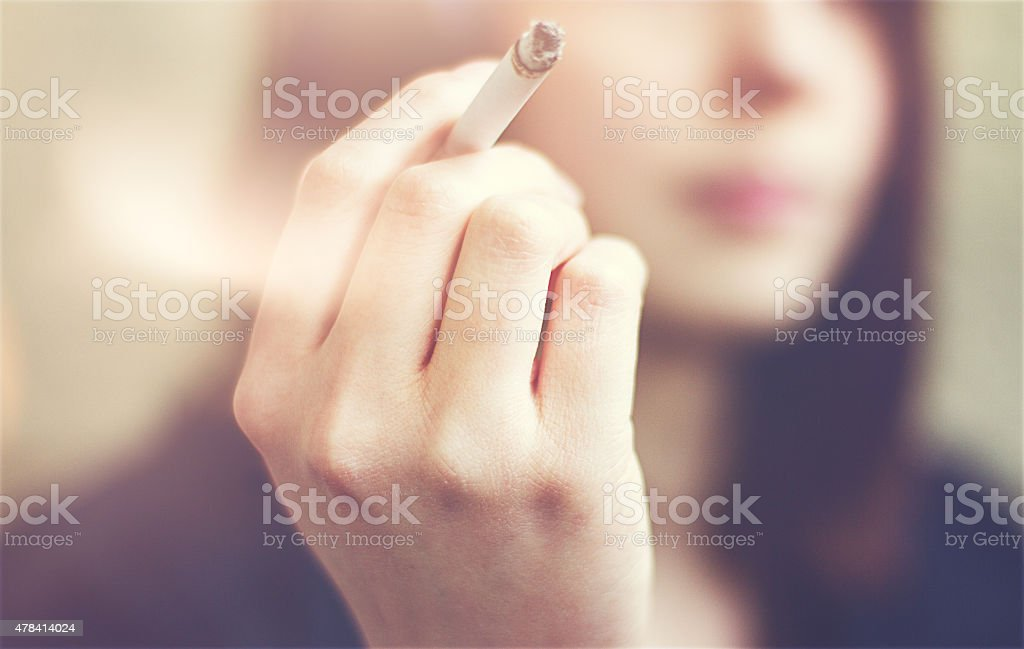 Woman hands holding cigarette outdoor. stock photo