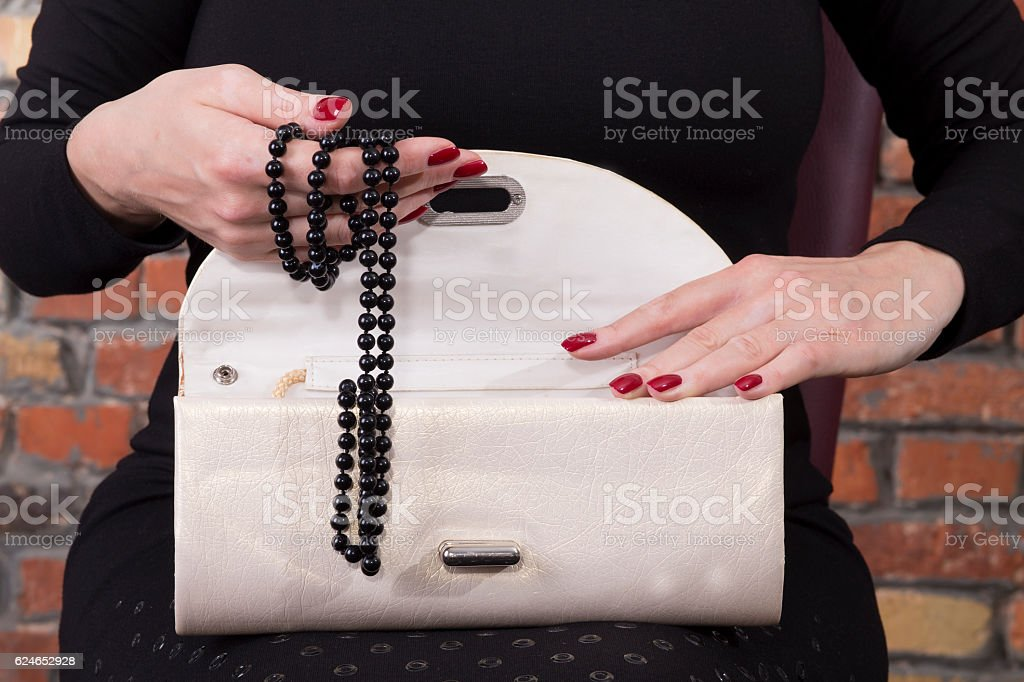 Woman hands holding fancy clutch with black pearl stock photo