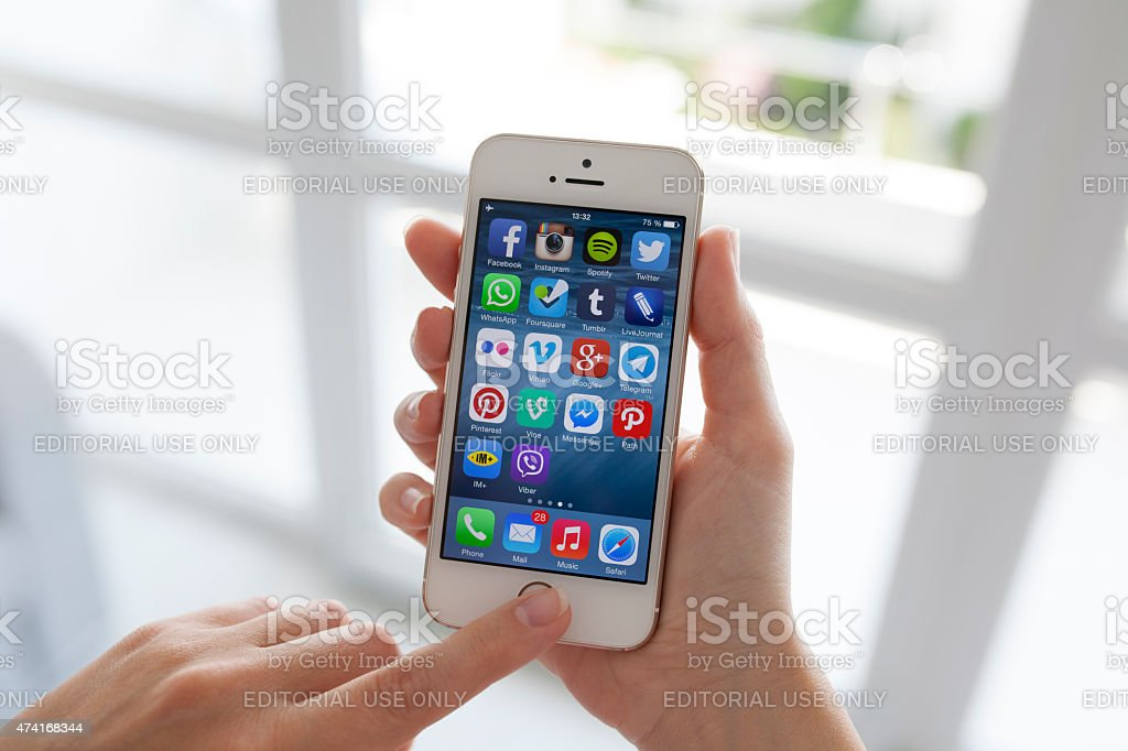 woman hands holding iPhone with social program on the screen stock photo