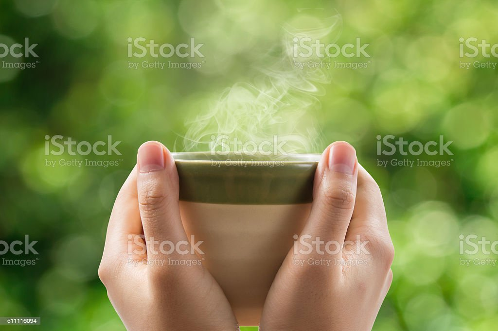 Woman hands holding tea cup on green bokeh background. stock photo