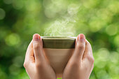 Woman hands holding tea cup on green bokeh background.