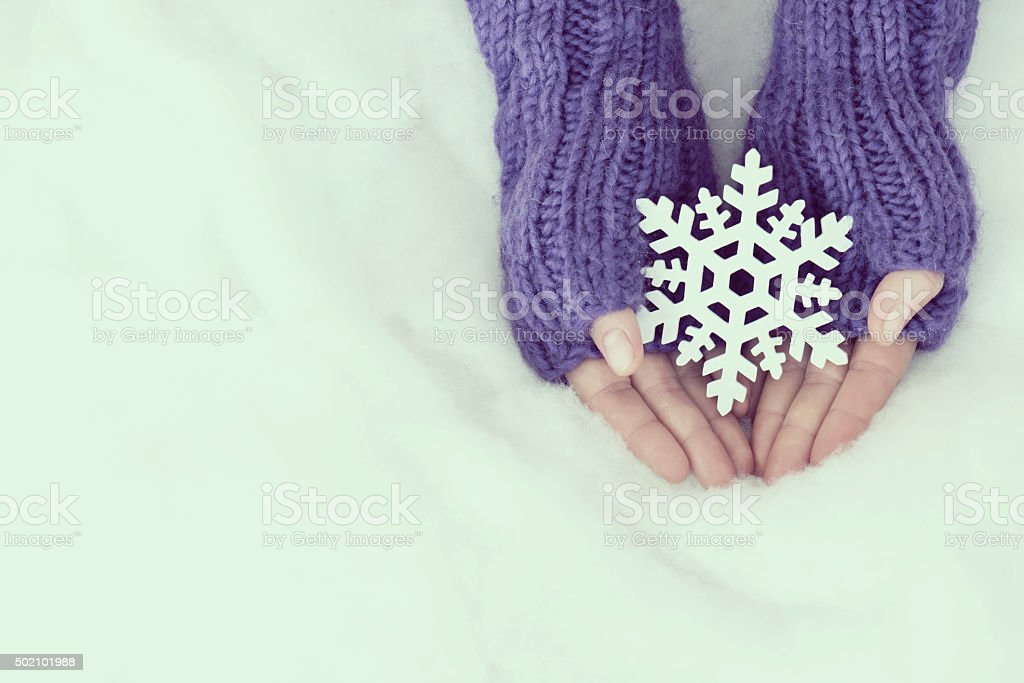 Woman hands in light teal knitted mittens are holding snowflake stock photo