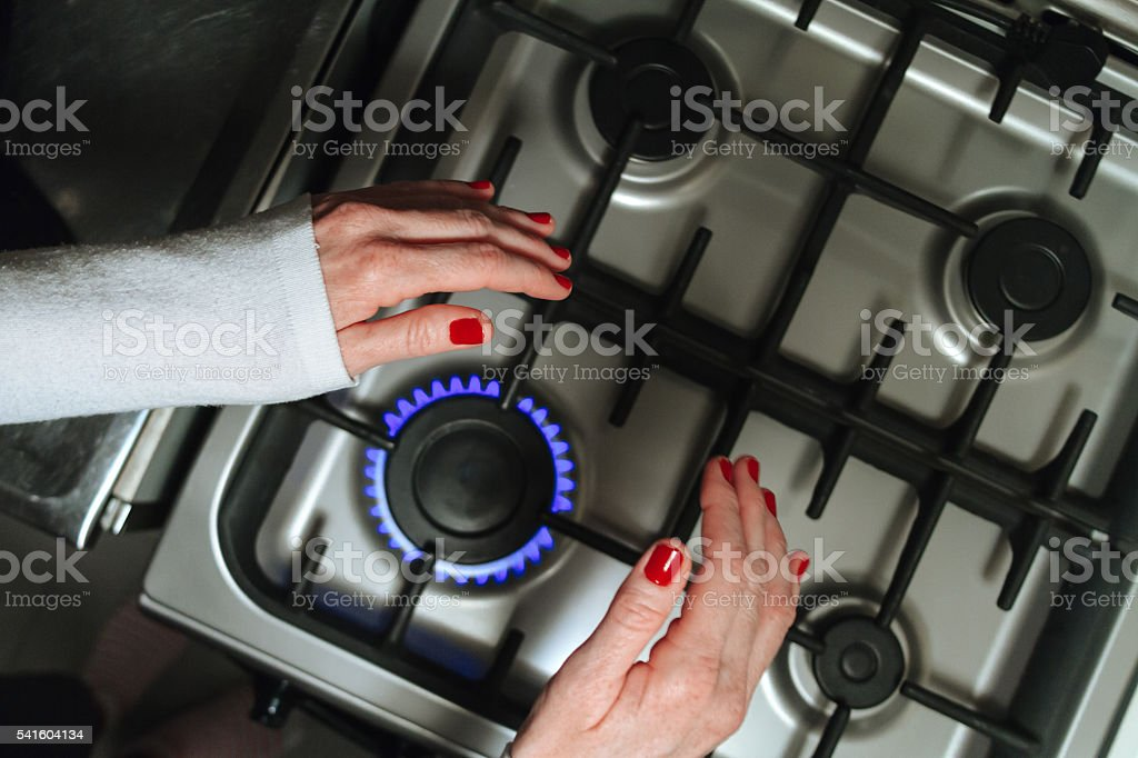 Woman hands on a burner heated stock photo
