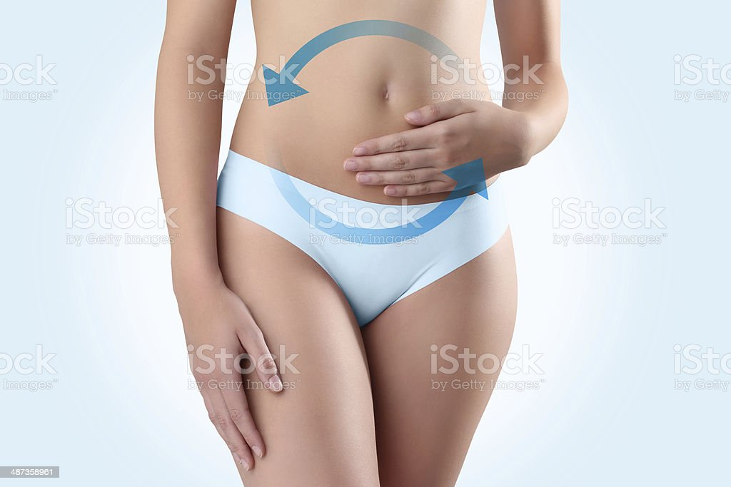 woman hands on belly with blue arrow stock photo