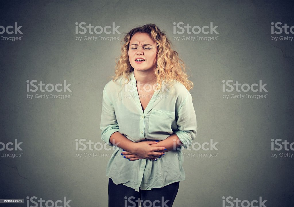woman hands on stomach having aches pain stock photo