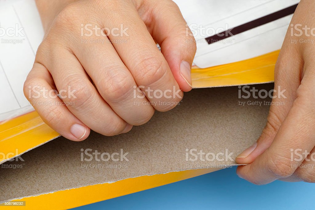 Woman hands open yellow package stock photo