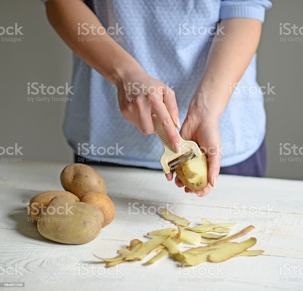 Woman hands peeling potatoes for boiling stock photo