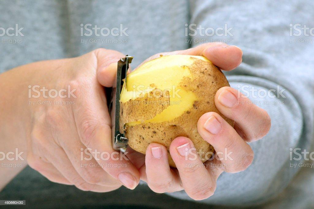 Woman hands peeling potatoes stock photo