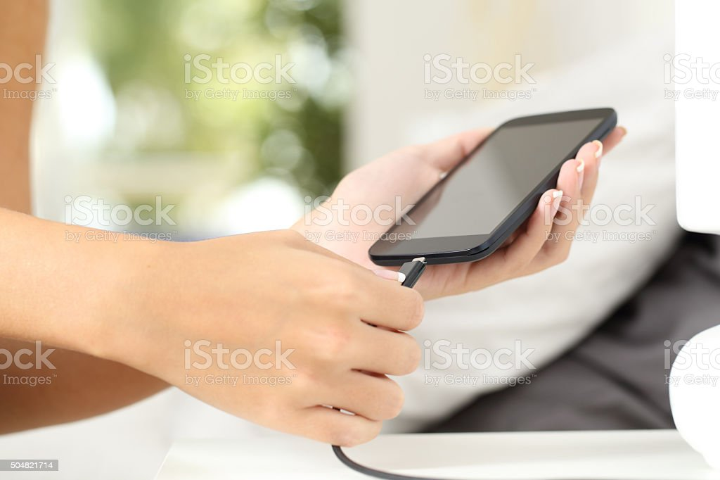 Woman hands plugging a charger in a smart phone stock photo