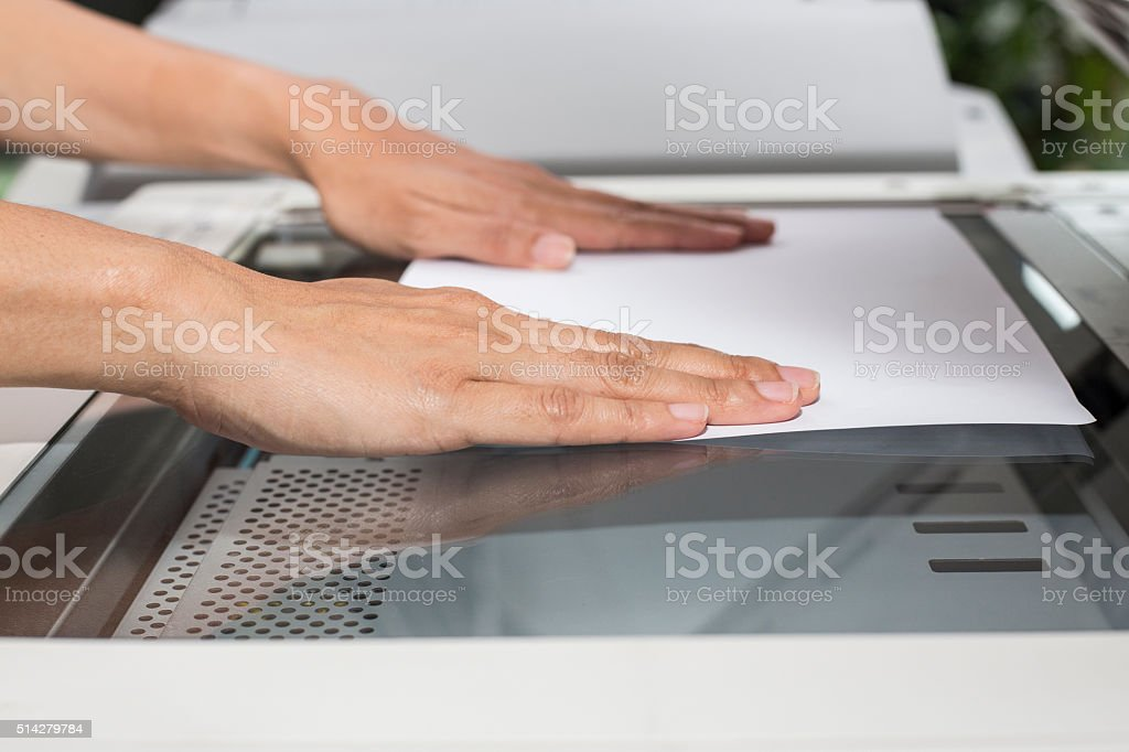 woman hands putting a sheet of paper stock photo