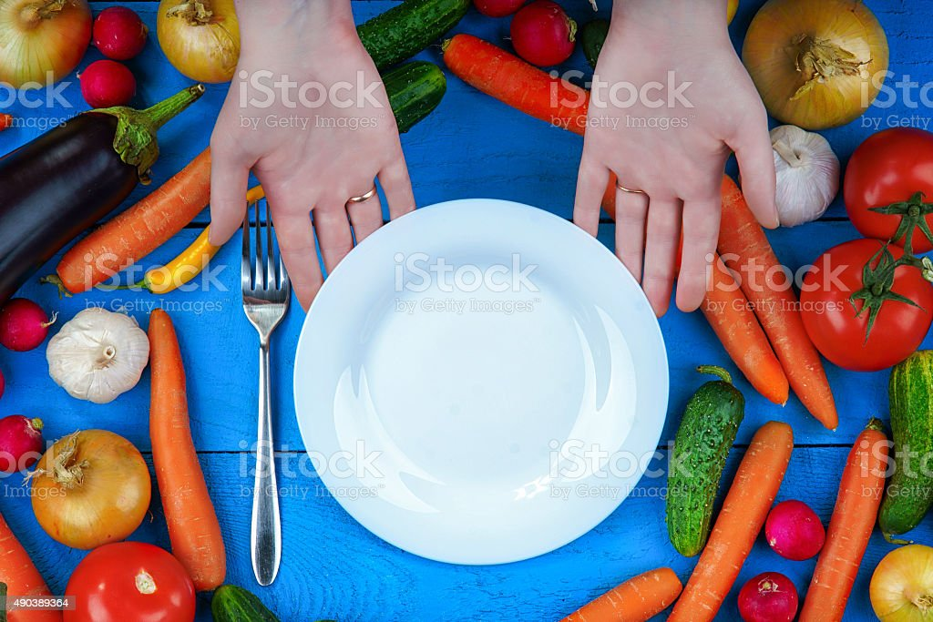 Woman hands serving empty plate among fresh vegetables stock photo