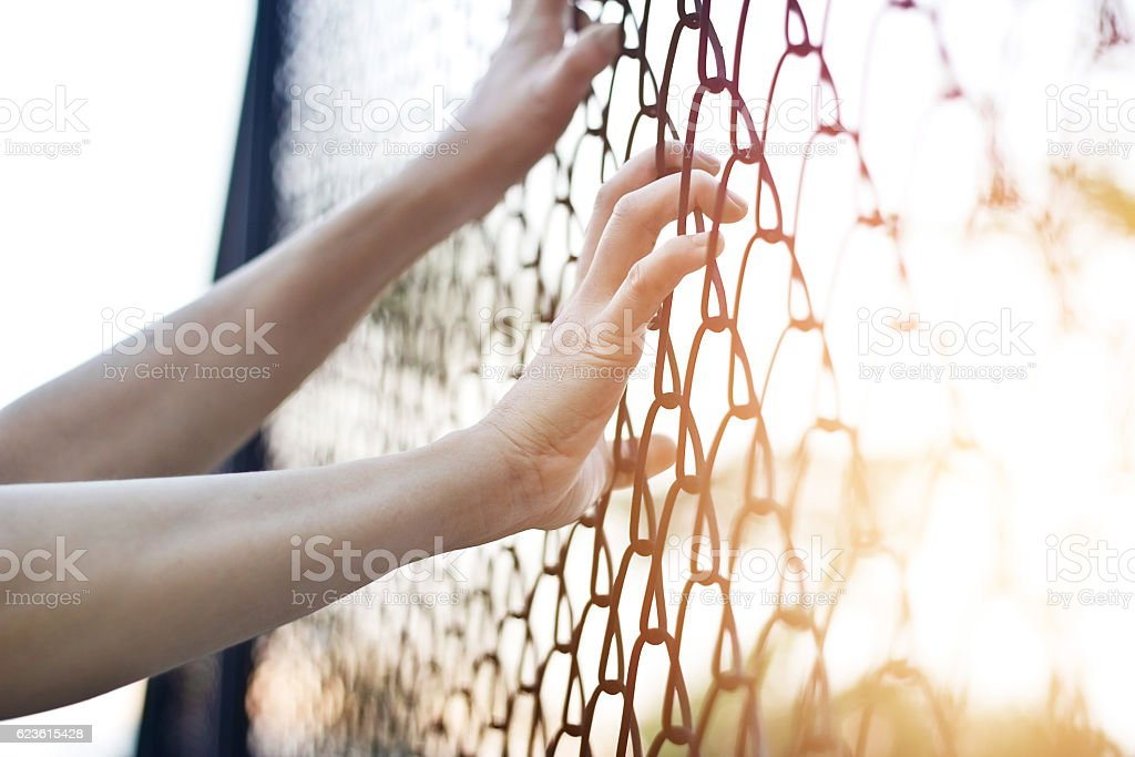 Woman hands touching a metal fence wire stock photo