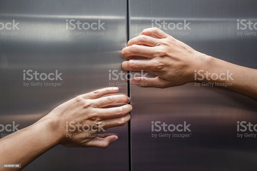 woman hands try to stop doors of the closed elevator stock photo