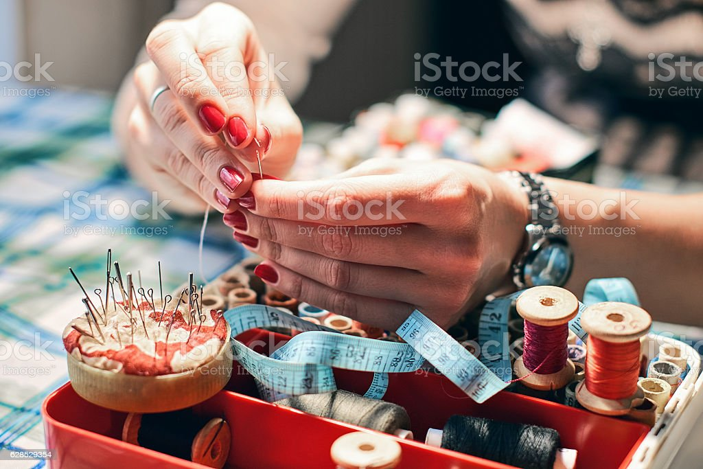 Woman hands trying to thread a needle stock photo