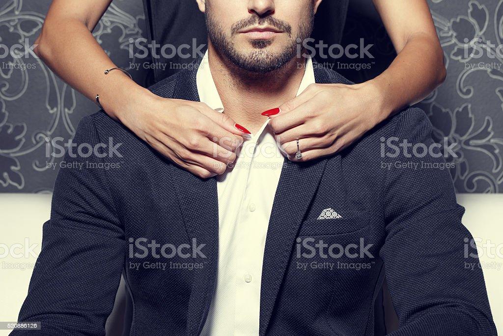 Woman hands undress rich man stock photo