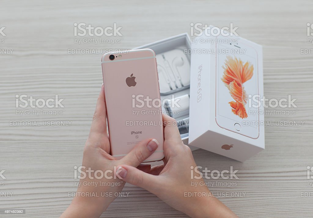 Woman hands unpacking iPhone 6S Rose Gold stock photo
