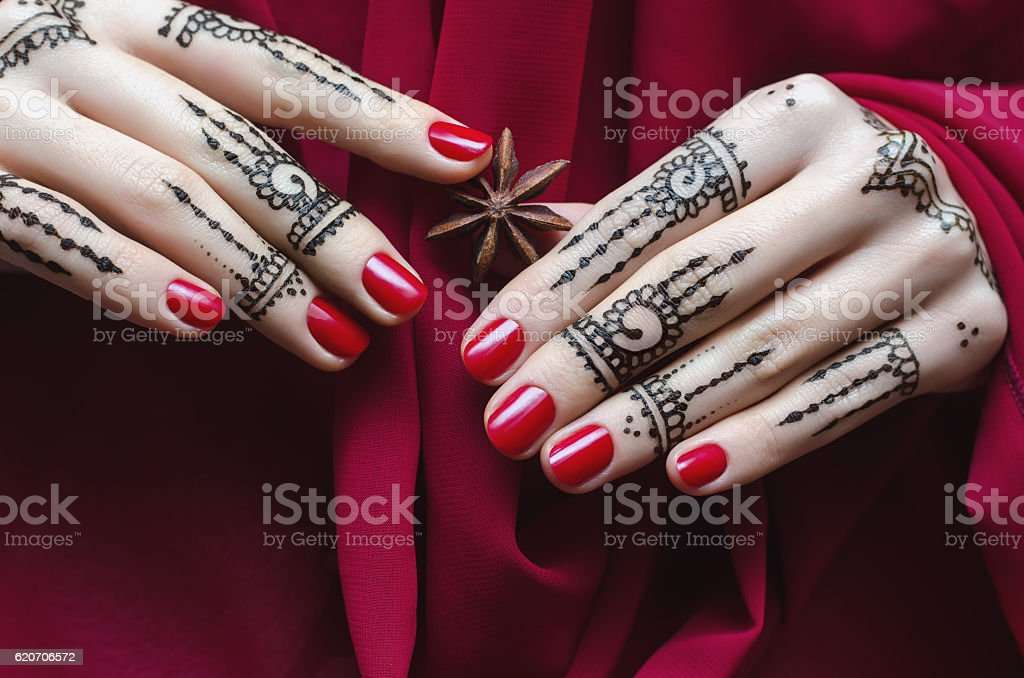 Woman Hands with black mehndi tattoo and ren manicure stock photo