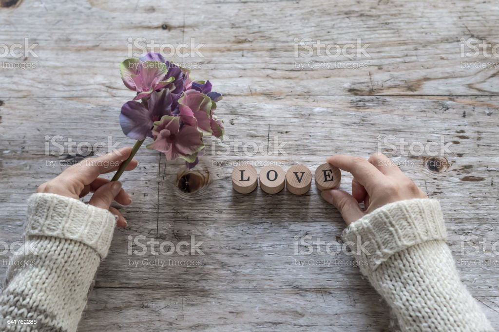 Woman hands with love word and flower stock photo