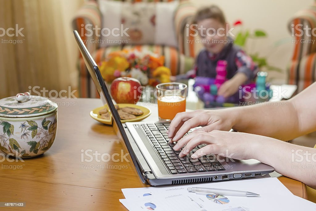 Woman hands writing in notebook and boy playing stock photo