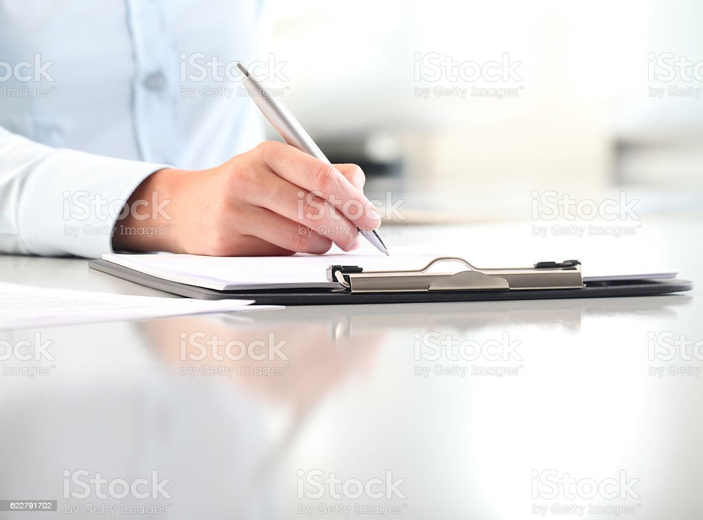 woman hands writing on clipboard with a pen stock photo