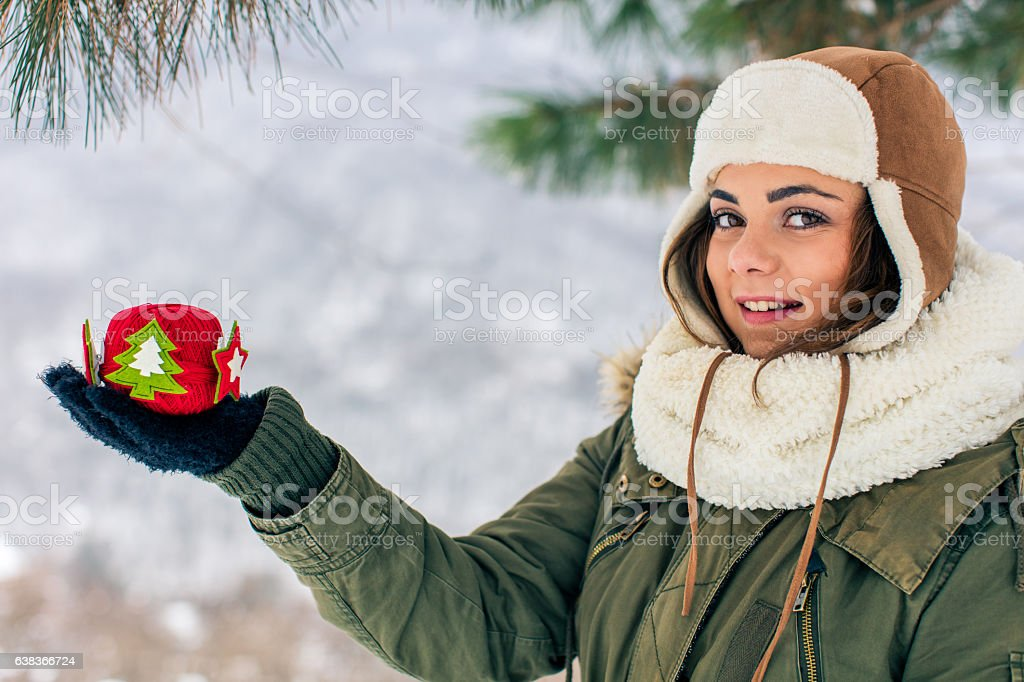 Woman hanging a colorful Christmas ornament in the snow stock photo