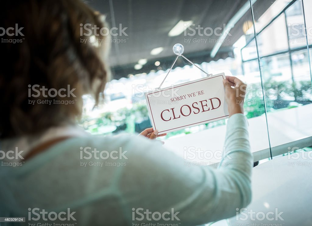 Woman hanging an closed sign at a small business stock photo