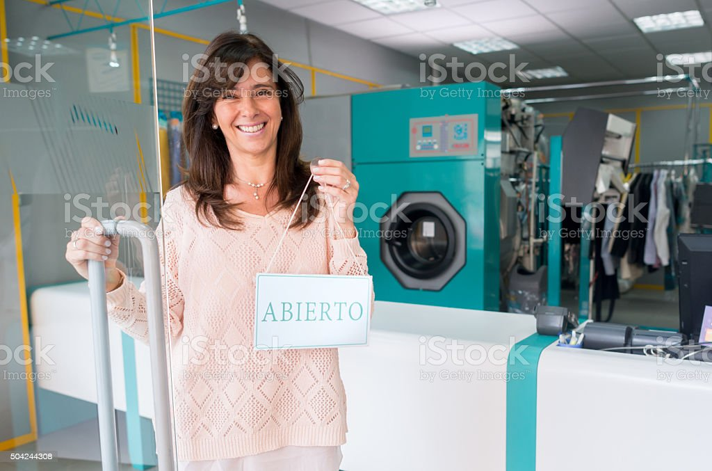 Woman hanging an open sign at a laundry shop stock photo