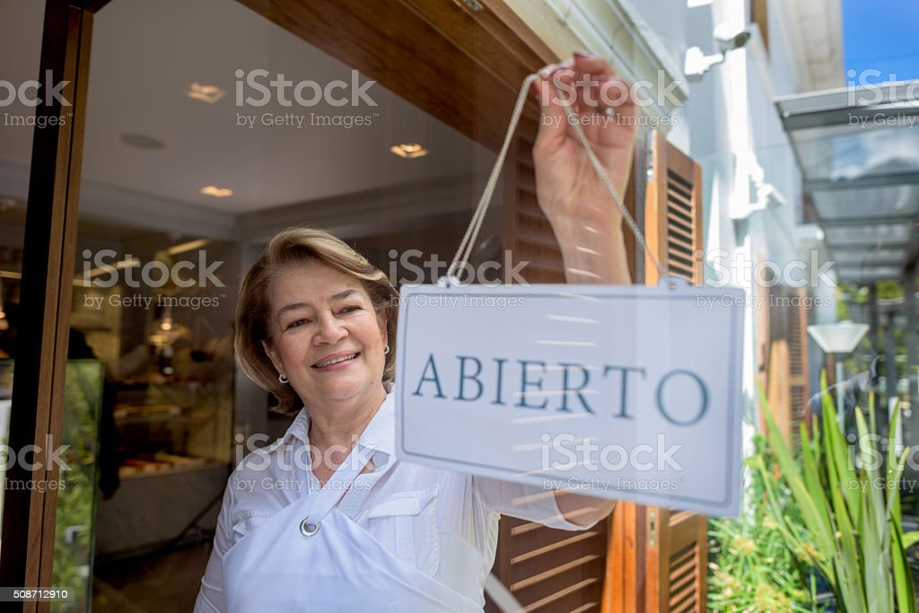 Woman hanging an open sign at the bakery stock photo
