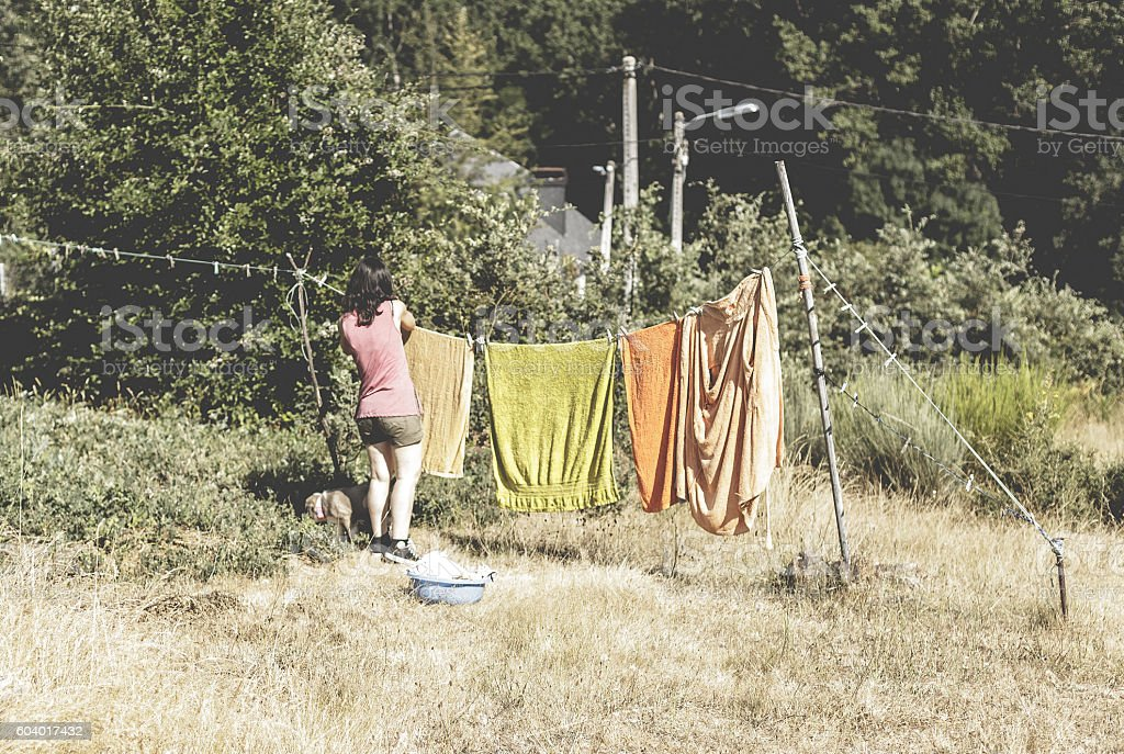 Woman hanging clothes on the line outdoors foto royalty-free