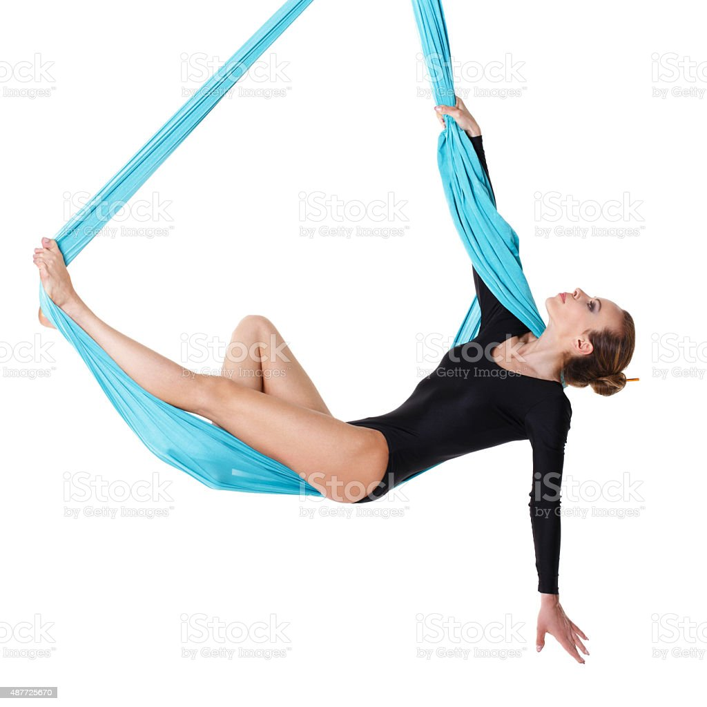 Woman hanging in aerial silk stock photo