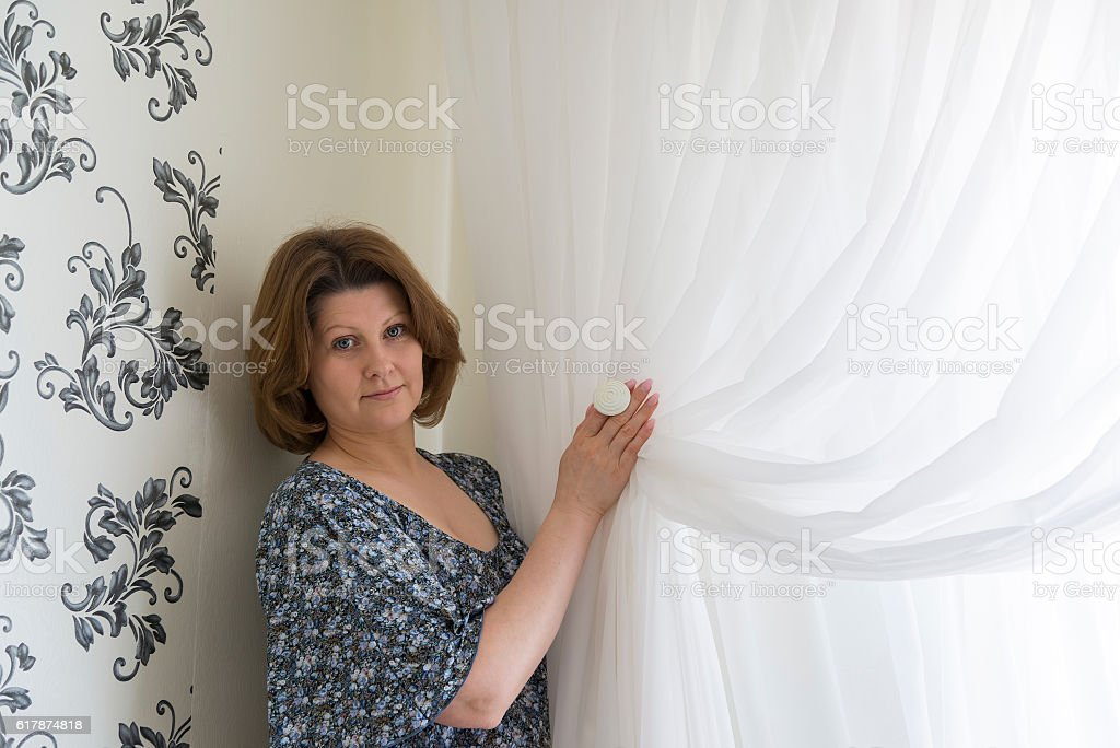 Woman hanging up his white curtains at window stock photo