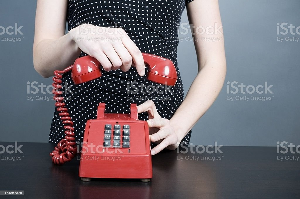 Woman hanging up old red telephone stock photo