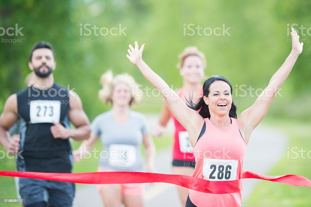 Woman Happily Crossing the Finish Line stock photo