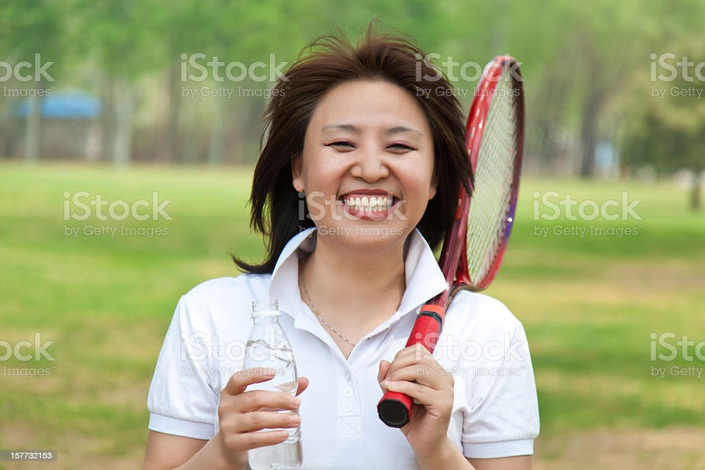 Woman happily holding mineral water and tennis racket royalty-free stock photo