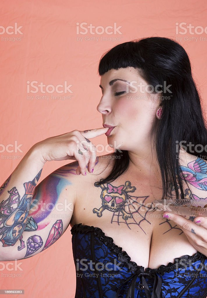 Woman happily licking crumbs off finger. royalty-free stock photo