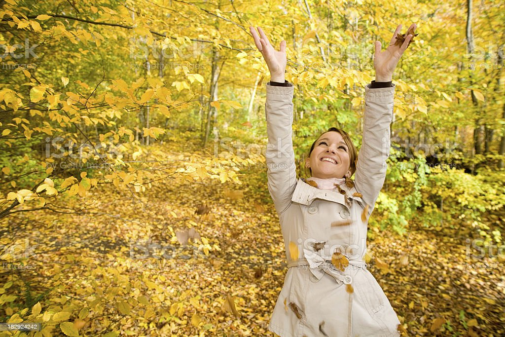 Woman happy about autumn and smiling reaching up royalty-free stock photo