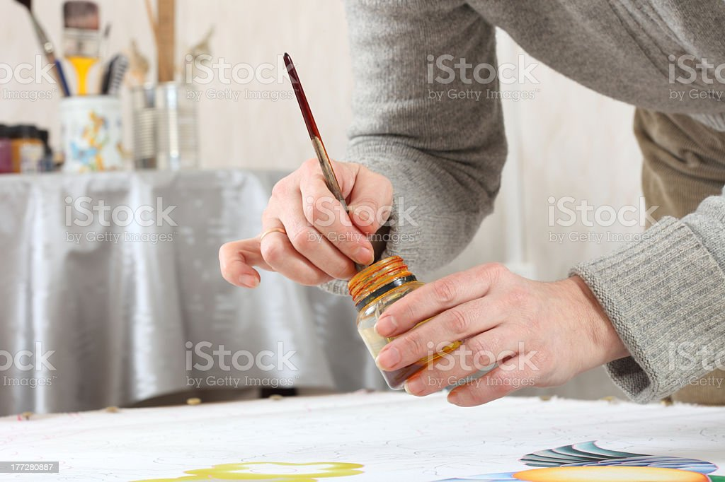 A woman hard at work hand painting some silk royalty-free stock photo