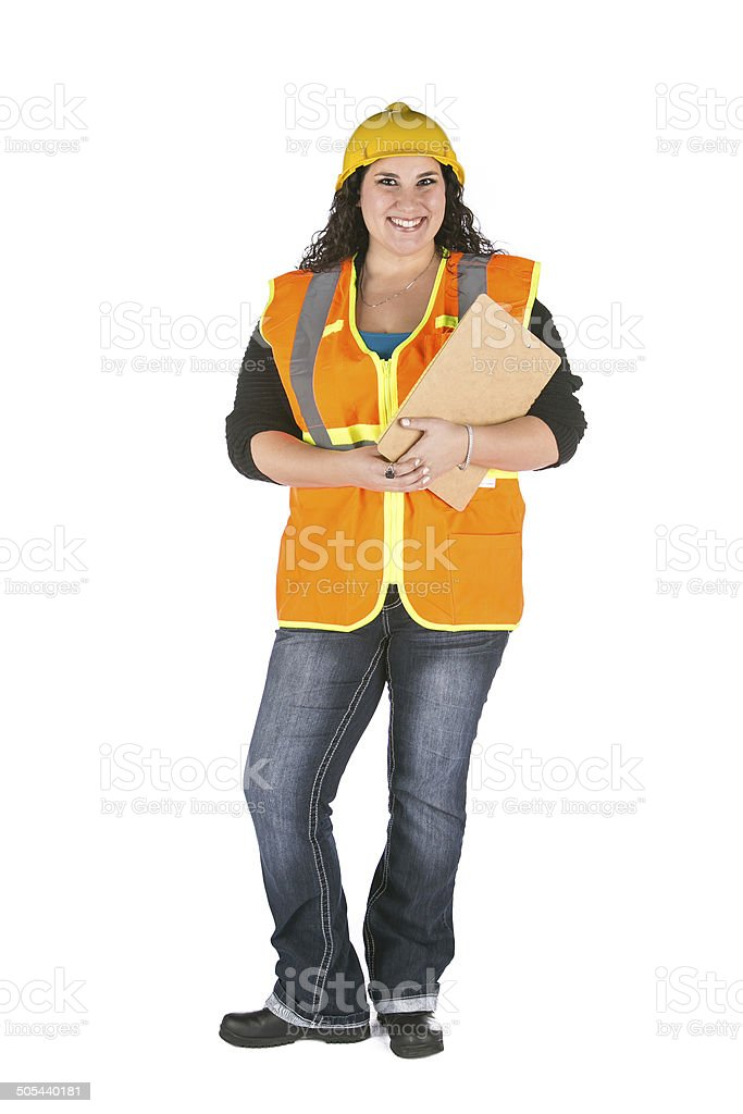 woman hardhat and safety vest holding clipboard stock photo