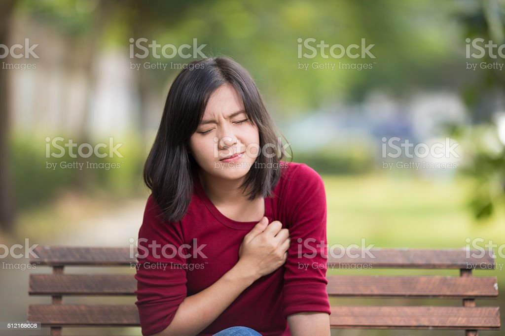 Woman Has Chest Pain Sitting on Bench at Park stock photo